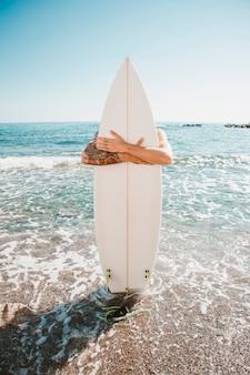 Man met surfplank op strand in de buurt van zee