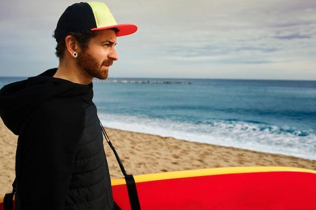 Man met surfplank op strand