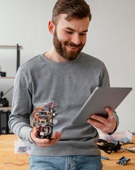 Man met tablet leren robot te maken