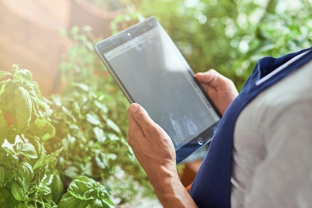 Man met tablet met actief scherm in kas