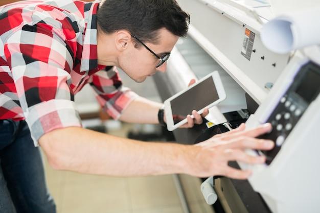 Man met tablet met behulp van printer