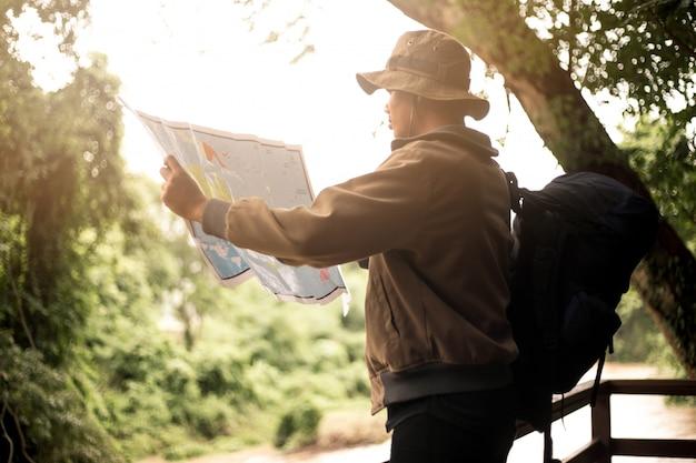 Man met tas, pet en met een kaart