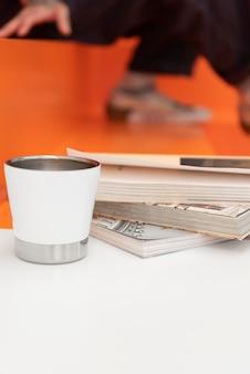 Man met tatoeages die koffie drinkt en een boek leest in café