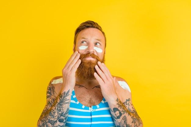 Man met tatoeages en zwembroek smeert zonnebrandcrème in