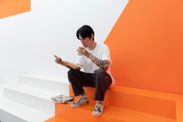 Man met tatoeages genieten van een kopje koffie in café en boeken lezen