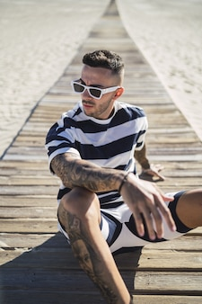 Man met tatoeages in modieuze kleding en zonnebril poserend op het strand