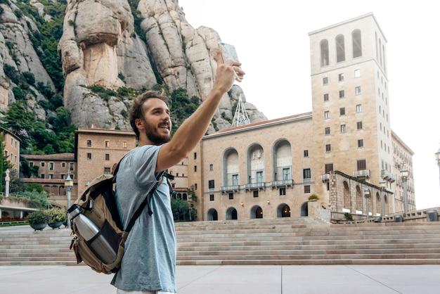 Man met telefoon die een selfiefoto neemt in het klooster van montserrat, barcelona, spanje