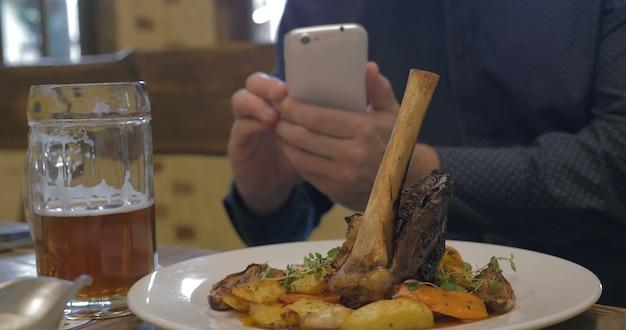 Man met telefoon die foto maakt van een geserveerd gerecht