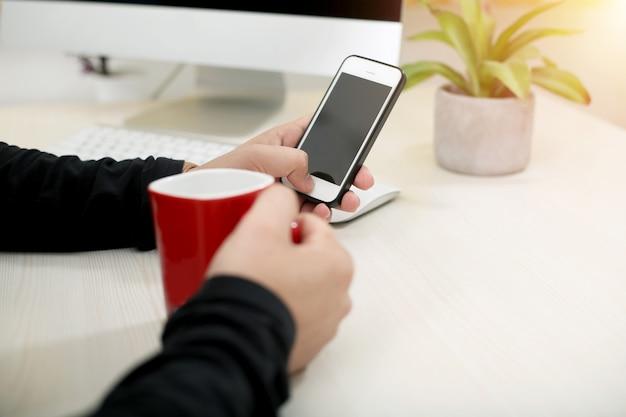Man met telefoon en koffiekopje in de hand.