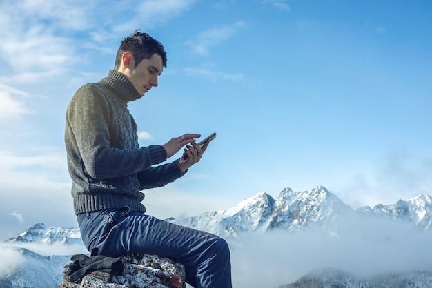 Man met telefoon in de hand op de top van een besneeuwde berg