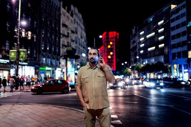 Man met telefoon in de straat van de stad