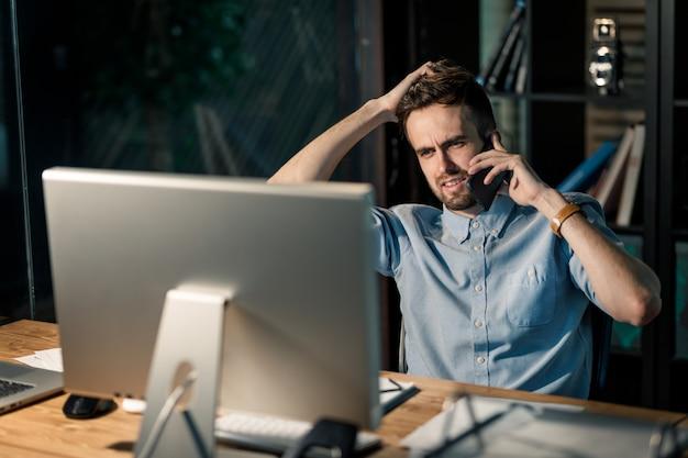 Man met telefoongesprek laat in kantoor
