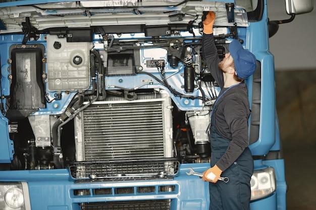 Man met tools voor vrachtwagen. werknemer in uniform. defecte truck