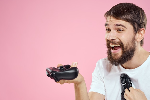 Man met twee joysticks in handen leuk spel technologie levensstijl roze
