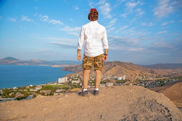 Man met uitzicht op een panoramisch uitzicht op een prachtige kustlijn vanaf de heuvel