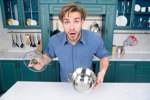 Man met verbaasd gezicht houdt pandeksel open in keuken man met kookpot voor stoofsoep
