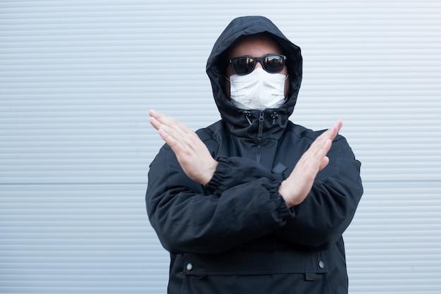 Man met verbodsbord op een neutrale muur, coronavirus, ziekte, infectie,