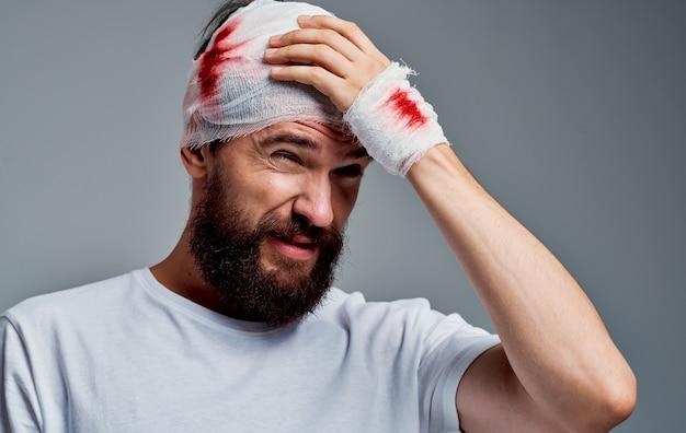 Man met verbonden hoofd en bloed hersenschudding grijze achtergrond geneeskunde