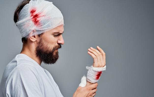 Man met verbonden hoofd en bloed hersenschudding grijze ruimte geneeskunde