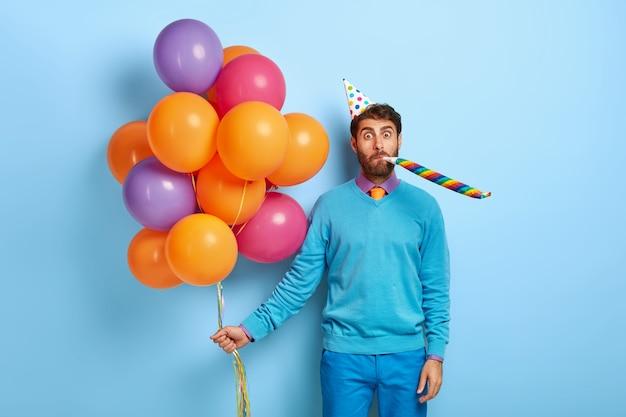 Man met verjaardagshoed en ballonnen poseren in blauwe trui