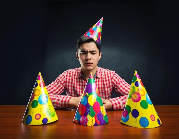 Man met verjaardagshoeden