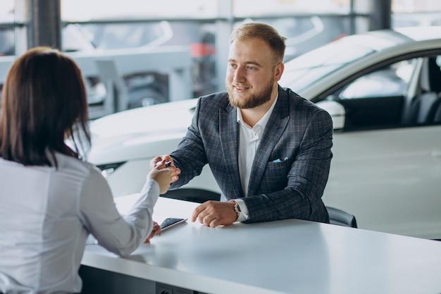 Man met verkoopvrouw in autoshowroom