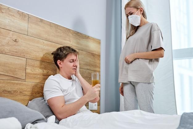 Man met verkoudheid, liggend op bed thuis, onwel en zijn vrouw in medisch masker zorgt voor hem door het geven van medicijnen, coronavirus, griepziekte. familie met ziekteverlof zelfisolatie concept