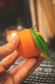 Man met verse mandarijnen op achtergrond van gezellige gebreide trui en kaars met boeken. hoge kwaliteit foto