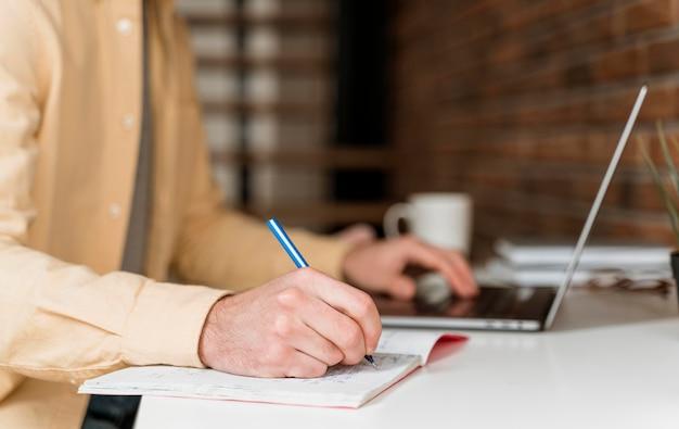 Man met video-oproep op laptop en schrijven
