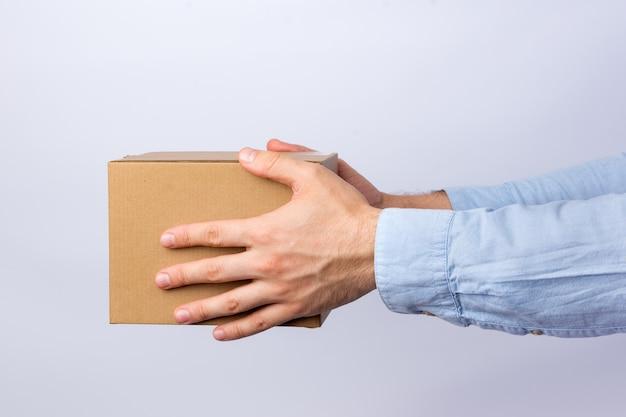 Man met vierkante kartonnen doos op arm's length. levering van pakketten. zijaanzicht.