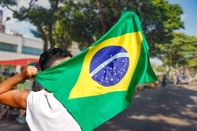 Man met vlag bij straatdemonstratie in brazilië.