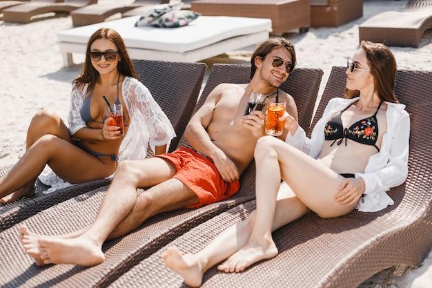 Man met vriendinnen zonnebaadt op het strand