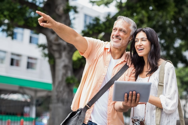 Man met vrouw die in stad richten terwijl het gebruiken van digitale tablet