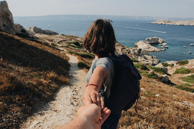 Man met vrouw hand in de buurt van de zee overdag