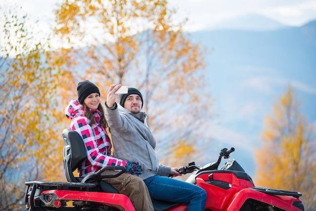 Man met vrouw op rode quad bike