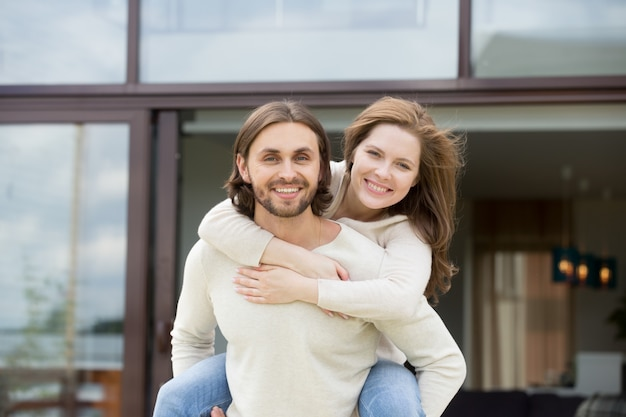 Man met vrouw op rug buitenshuis, kijkend naar de camera, portret