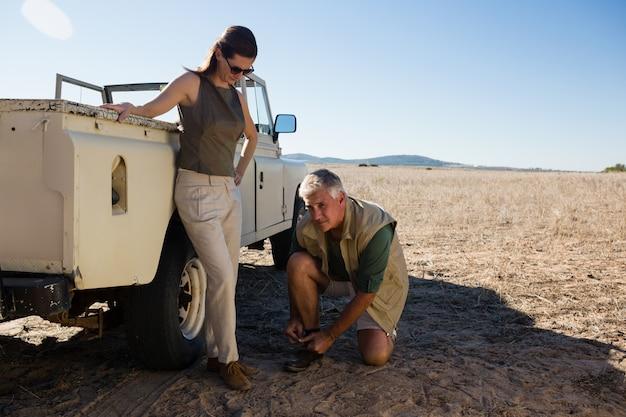 Man met vrouwen bindende schoenveter door voertuig op gebied