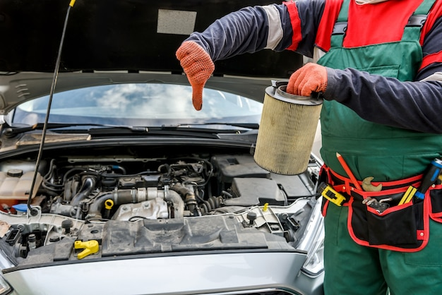 Man met vuile filter in de buurt van auto op workshop