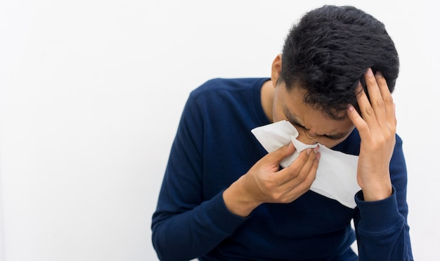Man met weefsel in de hand voor reactie niezen, gezond leven concept