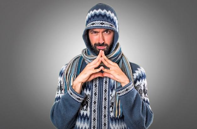 Man met winterkleding denken op grijze achtergrond