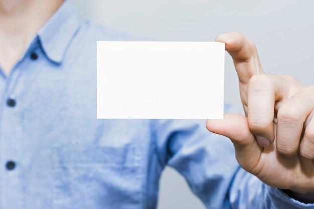 Man met wit visitekaartje op betonnen muur achtergrond, mockup sjabloon.