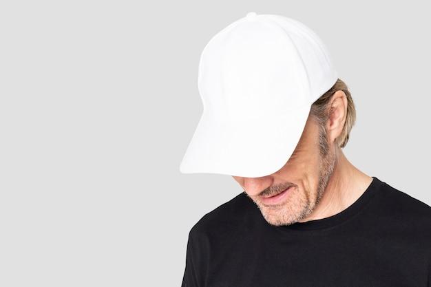 Man met witte pet voor fotoshoot voor herenkleding