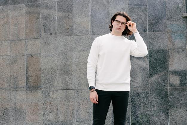 Man met witte sweater of hoodie en bril buiten op de straten van de stad.