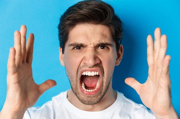 Man met woede en frustratie, schreeuwen met verontwaardigd gezicht, staande over blauwe muur