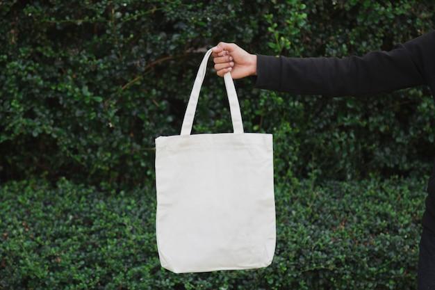 Man met zak canvas stof voor mockup, ecologie concept.