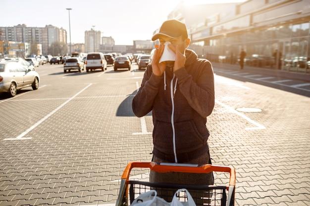 Man met zakdoek. ziek meisje heeft een loopneus. mannelijk model maakt een remedie voor de verkoudheid op de achtergrond van een parkeergarage.