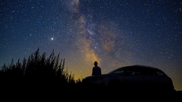 Man met zijn auto kijken naar hemel vol stralende sterren, lange blootstelling, moldavië