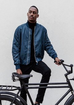 Man met zijn fiets naast een muur