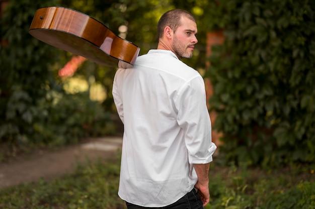 Man met zijn gitaar op zijn schouder van achter schot