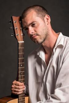 Man met zijn hoofd op gitaar headstock